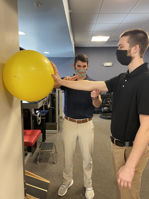 physical therapist shoulder rehab with ball