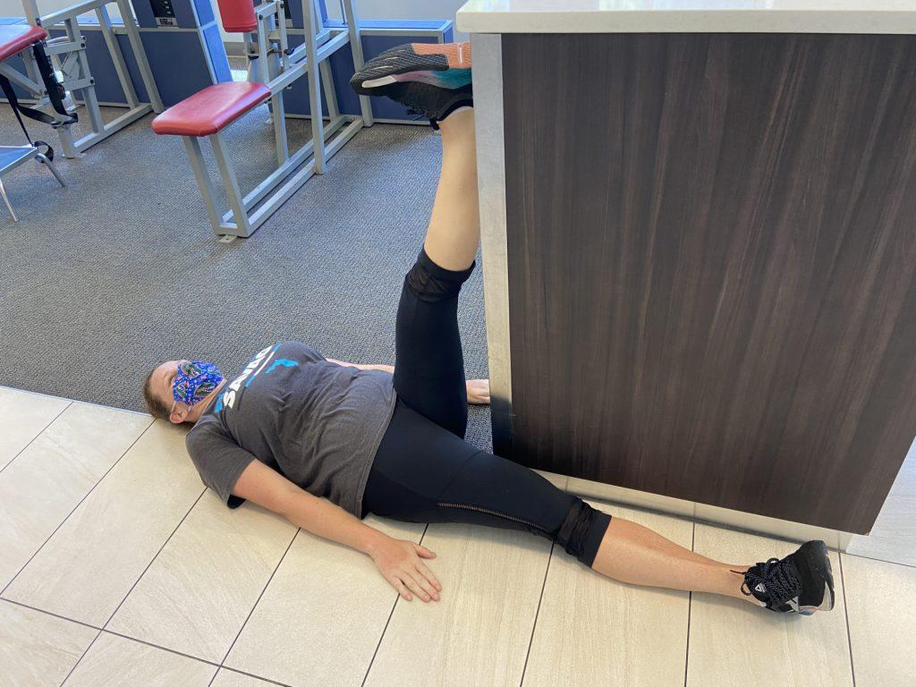 PNF stretching wall hamstring stretch