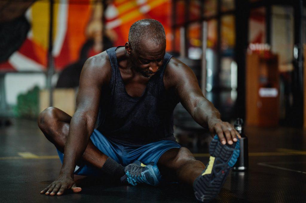man stretching legs at gym